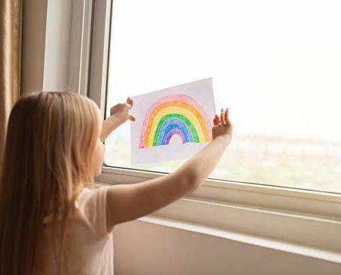 Kind mit gemaltem Regenbogen